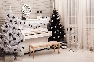 Black and White Christmas tree near white piano.