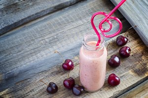 Cherry milkshake in a bottle and straw in the shape of heart. To