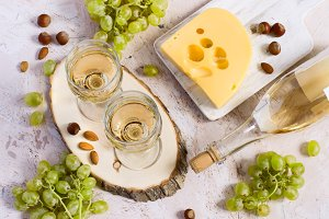 Two glasses of white wine, cheese and grapes. Top view