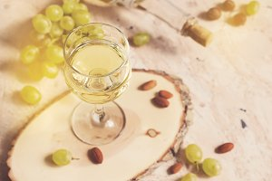 Glass of white wine on the background of grapes and nuts, tinted