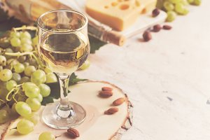 White wine in the glass on the background of grape and cheese