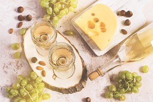 Two glasses of white wine, cheese and grapes. Top view, tinted