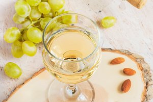 White wine in a glass and a bunch of grapes, tinted