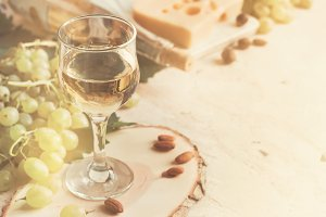 Vintage background with a glass of white wine and grapes, tinted