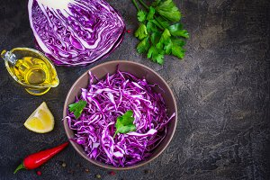 Purple cabbage salad and ingredients on a dark background.