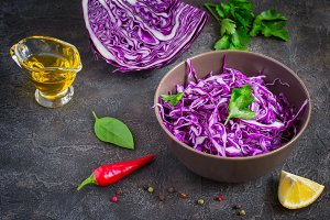 Purple cabbage salad and ingredients on a dark background