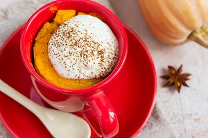 Autumn dessert of pumpkin baked in a cup, top view
