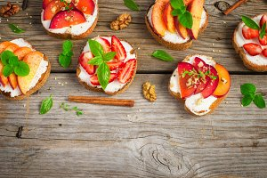 Summer breakfast bruschetta with plums, strawberries, peaches an