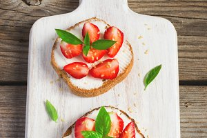 Summer breakfast bruschetta with strawberries, basil and cottage