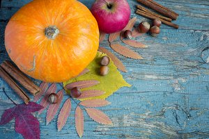 Pumpkin, nuts and leaves on the old wooden background.