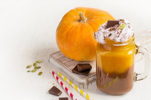 Pumpkin and chocolate smoothie with whipped cream, copy space