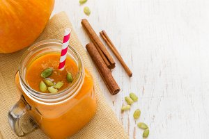 Pumpkin Smoothies with cinnamon in jar on a white background. To