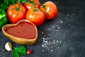 Tomato ketchup sauce with garlic, spices and herbs in wooden bow