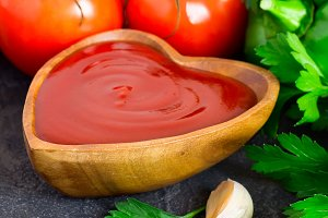 Tomato ketchup sauce with spices and herbs in wooden bowl close-