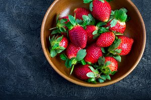 Juicy ripe strawberries in a wooden bowl closeup
