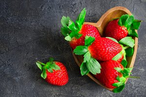 Juicy ripe strawberries in wooden bowl in the shape of heart