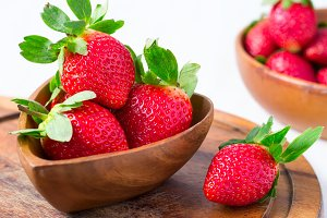 Ripe strawberries in a big wooden bowl, close-up, selective focu