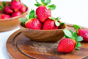 Ripe strawberries in a big wooden bowl, selective focus