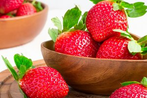 Ripe strawberries in a large wooden bowl, selective focus