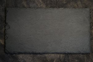 black slate board on dark stone background. Top view with copy s