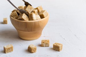 Brown sugar in a wooden bowl, selective focus