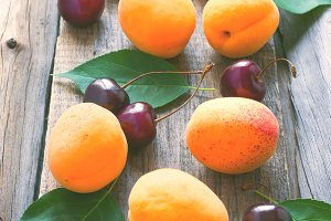 Ripe apricots and cherries are scattered on old wooden backgroun