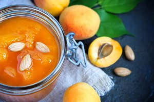 Fresh apricot jam in jar and ripe apricots close-up