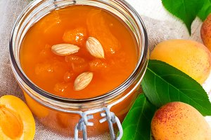 Fresh apricot jam in jar and ripe apricots