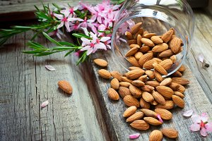 Flowers and almond nuts on a scattering of old wooden background