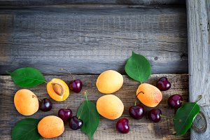 Fruity summer garden background with apricots and cherries. Top