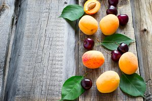 Country garden summer background with ripe apricots and cherries