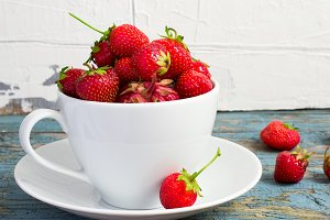 Ripe garden strawberries in white cup
