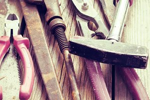 Background of old rusty tools and planks. Tinted.