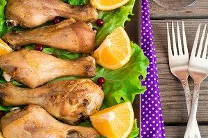 Dish with roasted chicken legs, greens, oranges and wine.