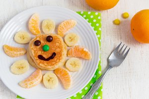 Pancakes with fruit for the children. Top view