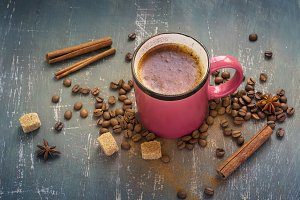 Hot pink coffee mug with cinnamon on old dark background.