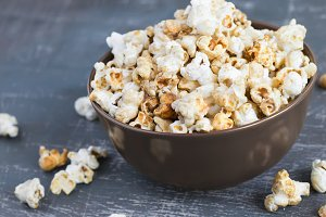 Sweet caramel popcorn in a  bowl on a dark blue background