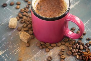 Cup of coffee with cinnamon, coffee beans and spices