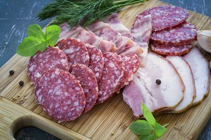 Meats - salami, bacon and greens on a cutting board