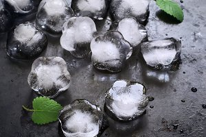Ice and mint leaves on a black background