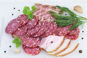 Slices of salami, bacon, spices and greens on white background