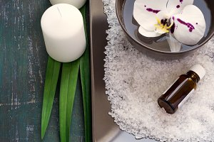 SPA setting with white orchid blossoms and sea salt and candles.