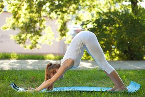 woman practices yoga on the nature