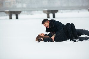 Girl and guy lie on snow