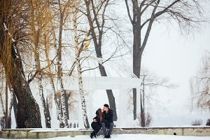 man and woman kissing in snowy park