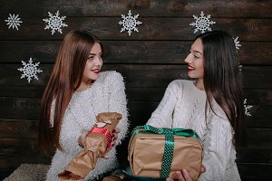 Two beautiful girls offer gifts to camera