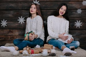 two beautiful girls give each other gifts