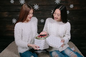 Two young girls holding holiday present
