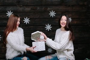 Two young girls holding bright holiday present