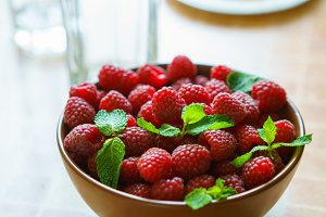 Pan over bowl of raspberries with mint.